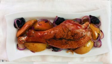 Roasted  turkey drumstick with apples, prunes and onions on white plate